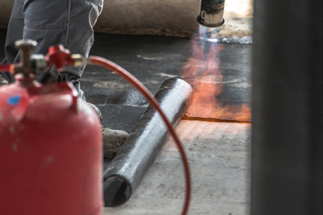 roofer next to propane gas torch, torching down a roofing membrane