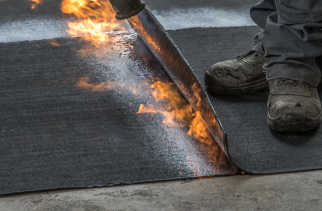 close up of a roofer torching down a membrane