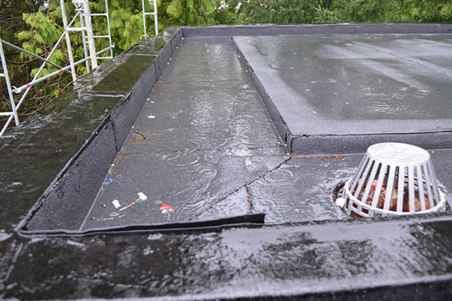 wet Commercial Roof and drain during rain
