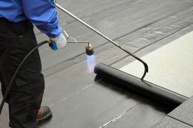 roofers torching down roofing membranes on a flat commercial roof