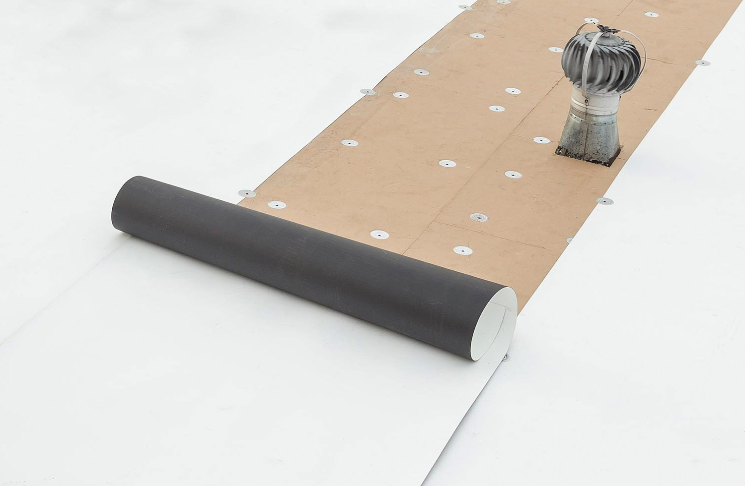 tpo membrane being rolled on top of mechanically fastened polyiso insulation