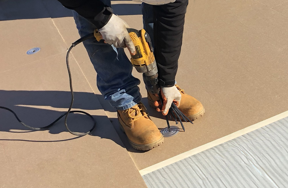 roofer fastening insulation board to roof substrate