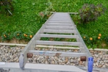extension ladder leaning on gutter - downward view