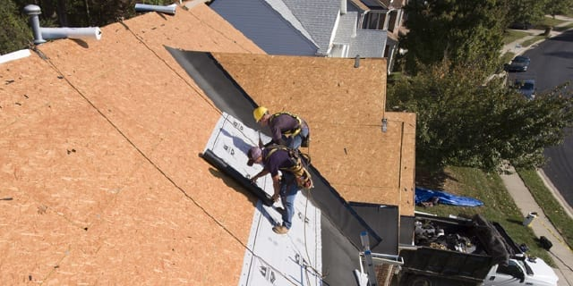 two roofers applying underlayment on a roof