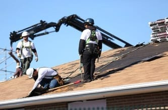 Roofers reparing a roof while roofing shingle bundles are being loaded onto the roof