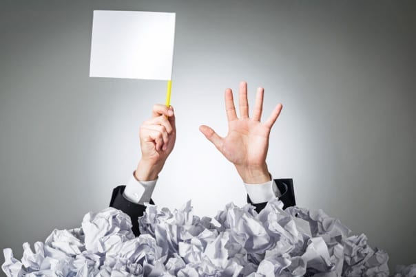 man buried under a pile of paper, waving a white flag