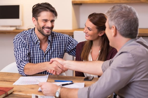 couple shaking contractors hand after signing roofing contract
