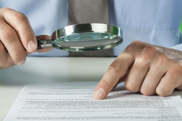 man using a magnifying glass to read the fine print on a roofing contract