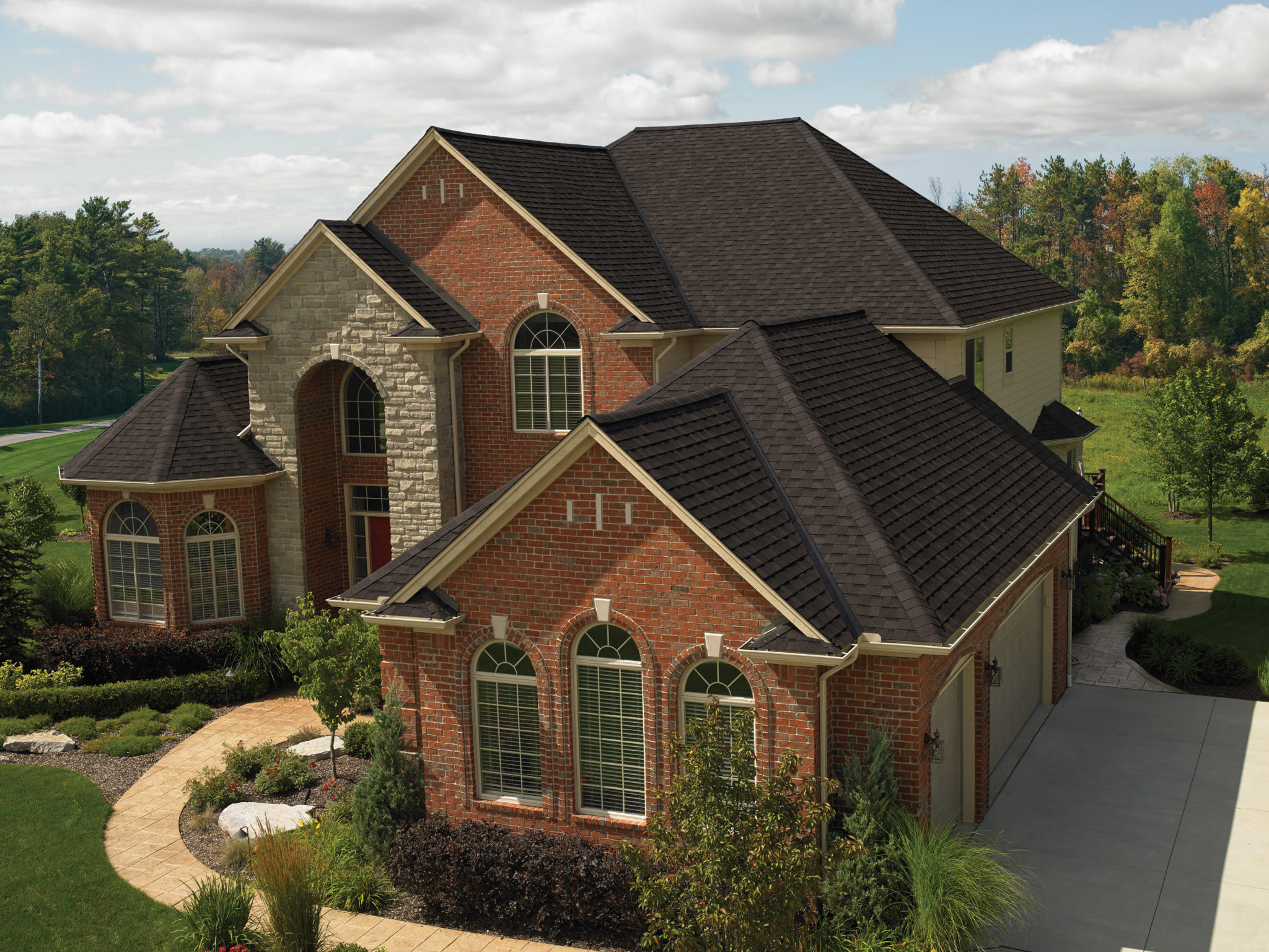 smoky red brick house with dark brown-black roof shingles