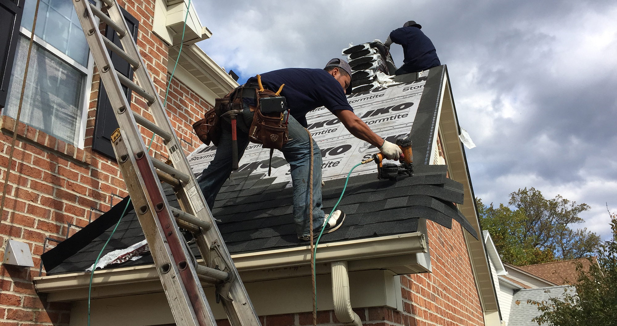roofer shingling with a nail gun