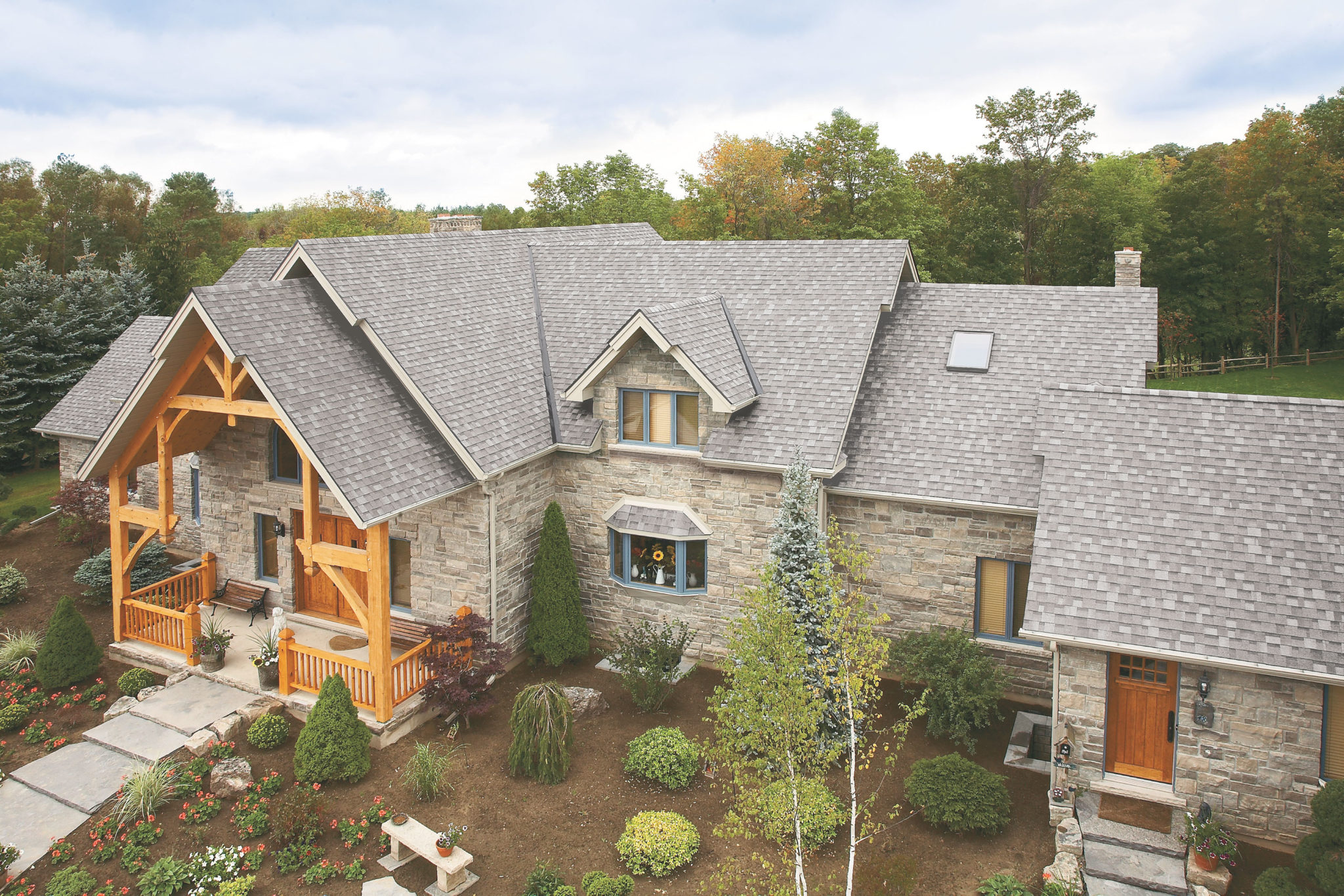 rural stone home with grey roof shingles