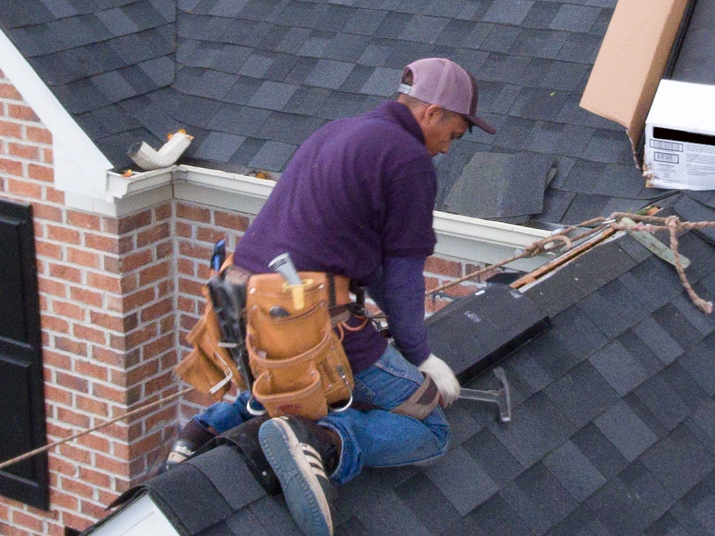 roofer using a roofing hatchet to install ridge cap shingles