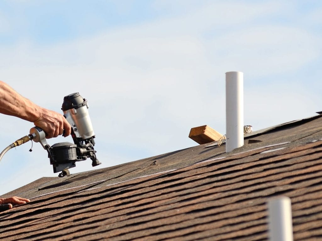 roofer installing shingles close to a roof ridge