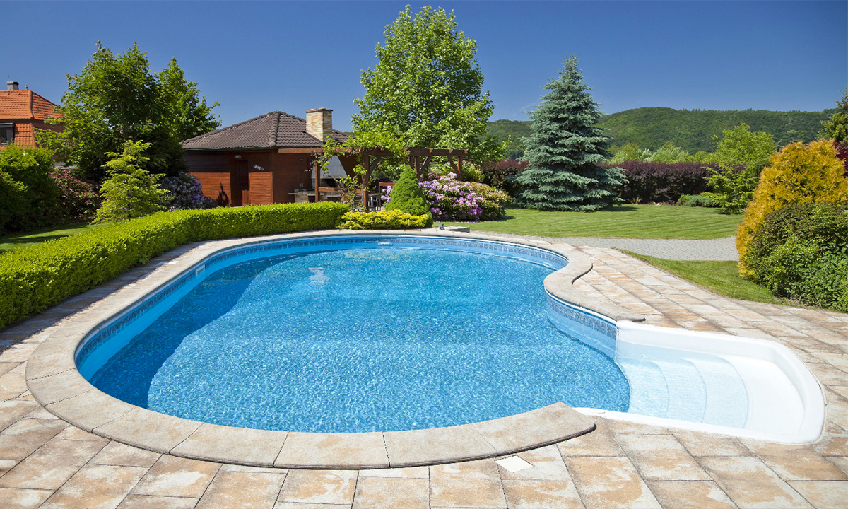 backyard pool next to house with brown shingles