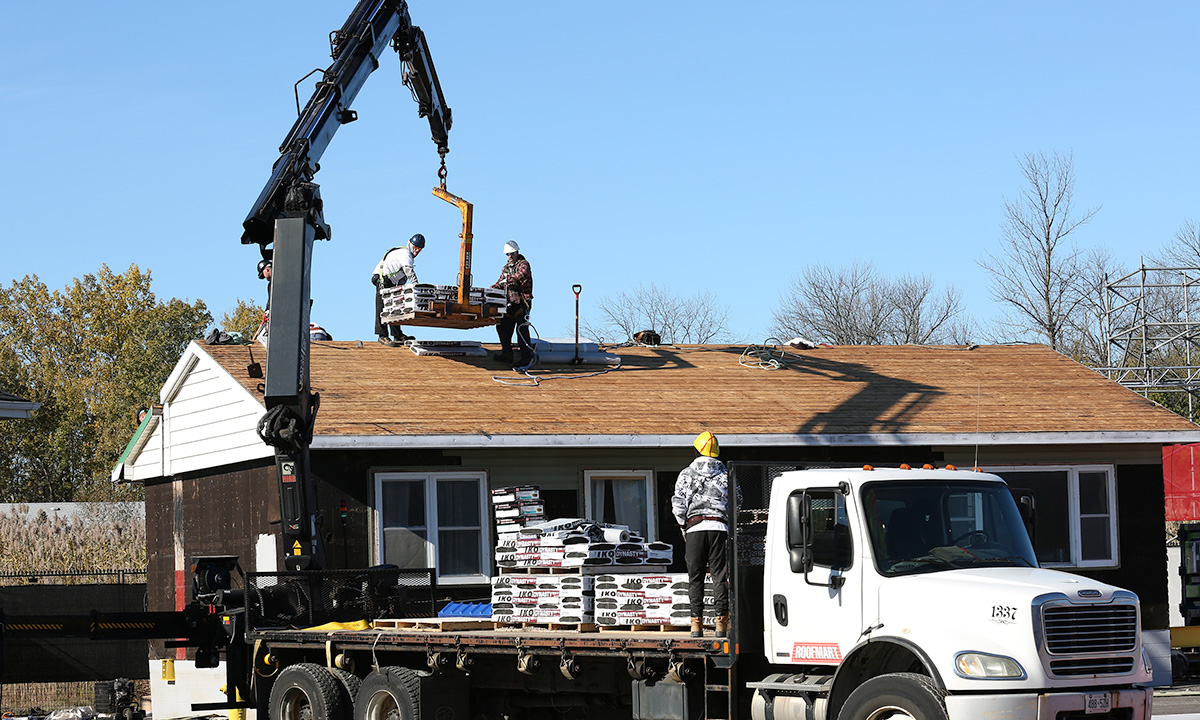 Boom truck lifting shingles to the top of a roof