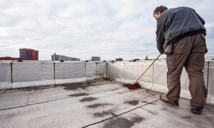 worker sweeping debris on a flat roof