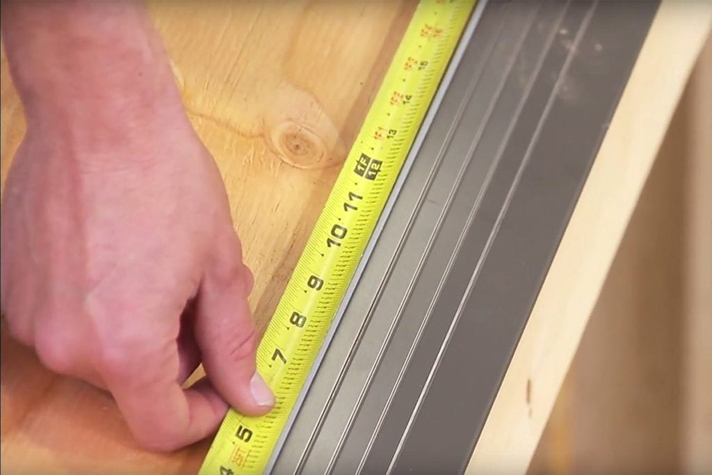 using a tape measure to confirm nail location on a drip edge
