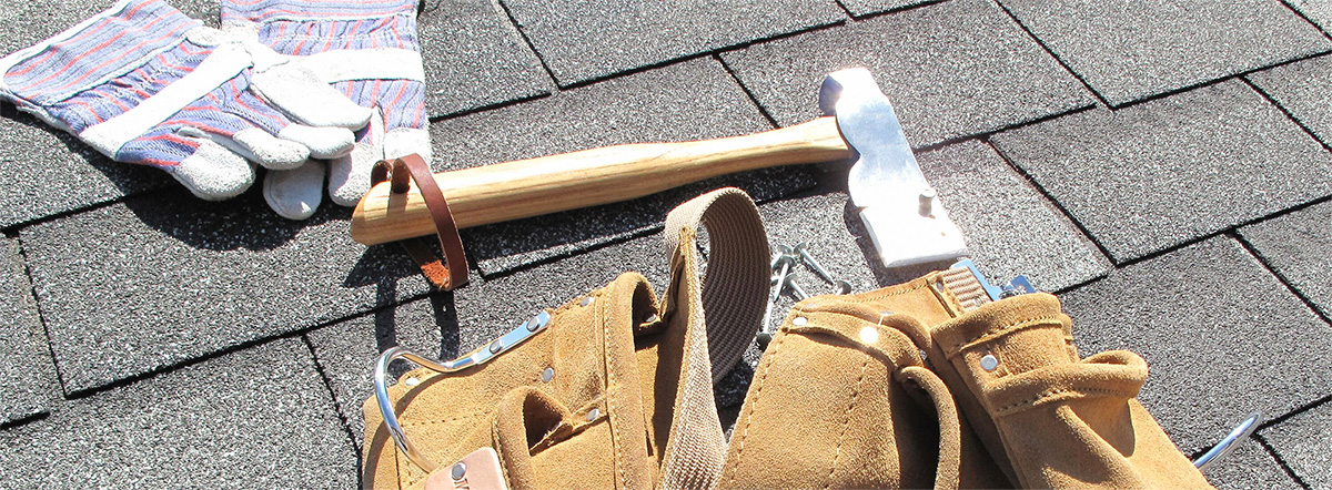 roofing tools on a shingle roof