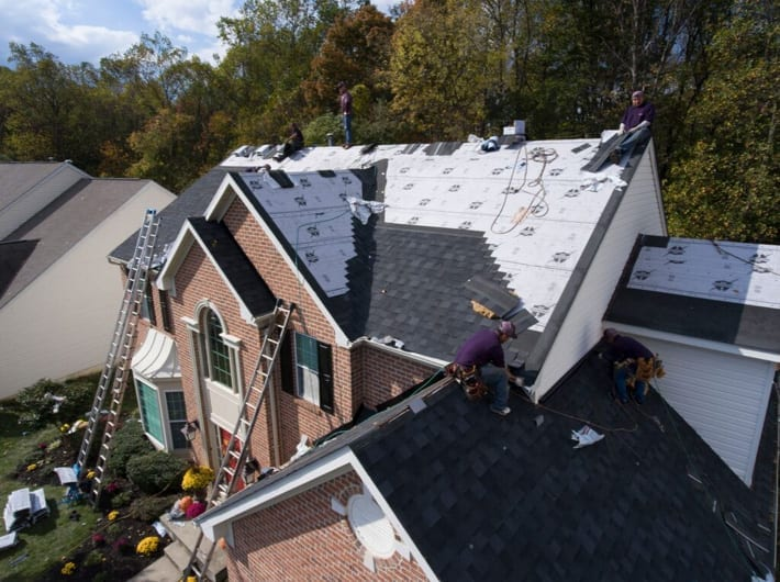 Roofers applying underlayment and shingles